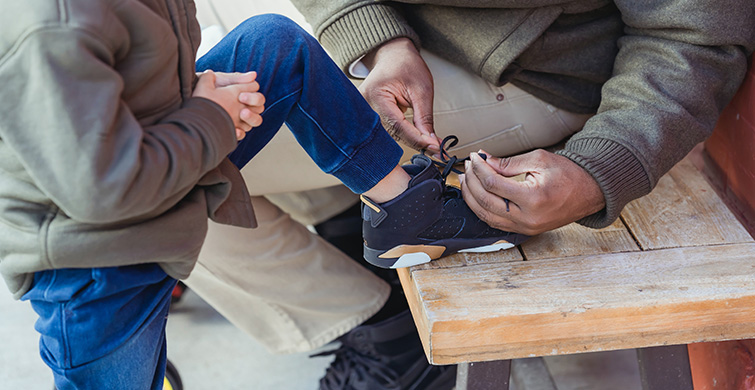 An adult fixes a child's shoelaces.